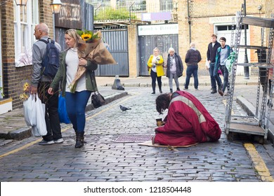 LONDON, ENGLAND - October 12, 2018 A beggar man with a glass in his hand asks for alms. Crowd pass by