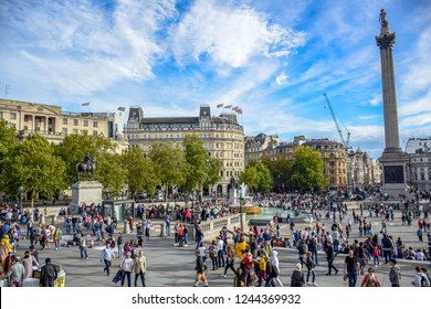 LONDON, ENGLAND - OCTOBER 23: Locals and tourists visiting and hanging out at a very busy Trafalgar Square in the City of Westminster, Central London, England, United Kingdom