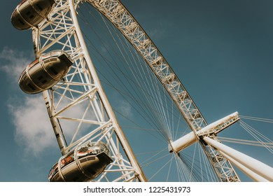 LONDON, ENGLAND - October 25th, 2018: The London Eye ferris wheel viewed from the ground with a blue sky background, during a beautiful sunset at The Queen's Walk.