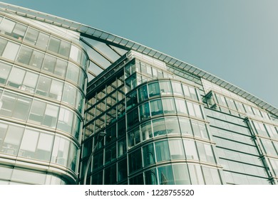 LONDON, ENGLAND - October 25th, 2018: Close up detail of modern glass building, with business offices inside, with daylight and blue sky background.