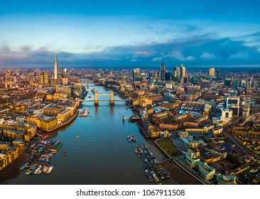 London, England - Panoramic aerial skyline view of London including Tower Bridge with red double-decker bus, Tower of London, skyscrapers of Bank District and Shard skyscraper at golden hour