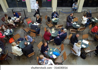London, England - Sept 09, 2015: People seated at tables provided by a cafe in the indoor area of Covent Garden in London, England. The area receives over 40 million visitors a year