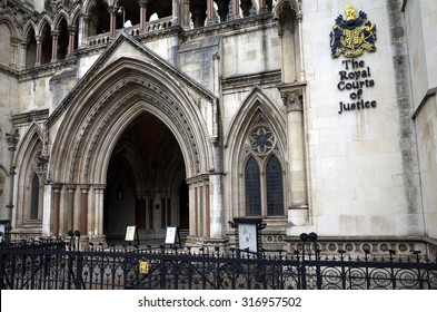London, England - Sept 09, 2015: Exterior facade of the Royal Courts of Justice in London, England showing the coat of arms of the courts and the archway of the main entrance