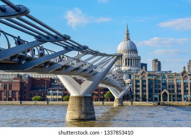 London, England - September 1, 2018: View of St Paul's Cathedral with people crossing the Millenium Bridge in London on a sunny summer day.