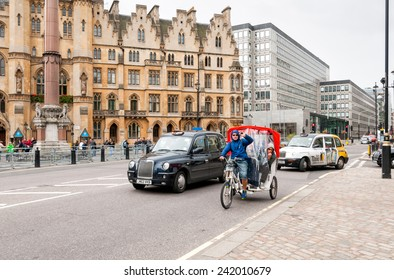 LONDON, ENGLAND - SEPTEMBER 15, 2013: Men on motor tricycle on the road in London city.