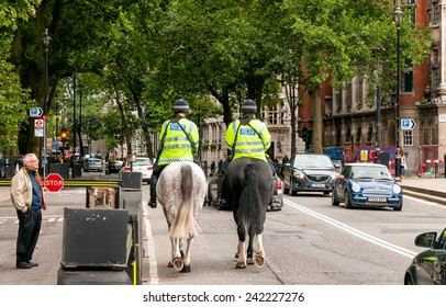 LONDON, ENGLAND - SEPTEMBER 15, 2013:  The Metropolitan Police with special police horses to keep the crowds under control, they sauntering around London