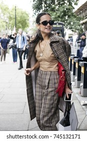 LONDON, ENGLAND - September 15, 2017 girl with her hair tucked into her tail in a classic checkered suit from Burberry poses during the London Fashion Week