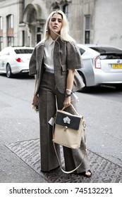 LONDON, ENGLAND - September 15, 2017 Blonde girl in gray pantsuit posing during London Fashion Week