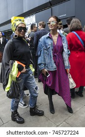 LONDON, ENGLAND - September 15, 2017 Two girlfriends in a jeans jacket and a colorful dress posing during the London Fashion Week