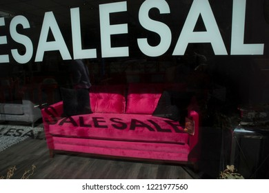 LONDON, ENGLAND - September 15, 2018 Red sofa in the shop window. Inscription on the glass - sale. The shadow of the inscription on the couch.