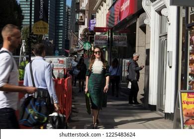 LONDON, ENGLAND - September 15, 2018 A woman wears nice green dress walk down the street