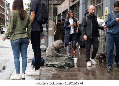 LONDON, ENGLAND - September 15, 2019 A beggar woman on her knees sits on the street, the crowd goes by