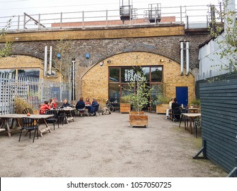 LONDON. ENGLAND - SEPTEMBER 16; Rustic trendy style cafe and bakery built in structural arch of bridge with patrons dining outdoors in Bow suburb on September 16 2017 London England