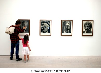 "LONDON, ENGLAND - SEPTEMBER 29, 2013: Father and his daughter view the artworks in Saatchi Gallery's ""Paper"" exhibition in London."