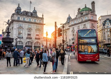 LONDON, ENGLAND -SEPTEMBER 9, 2018: View of the famous Piccadilly Circus square in London, England at sunset with lots of locals and tourists passing by and the double deck red bus on its way.