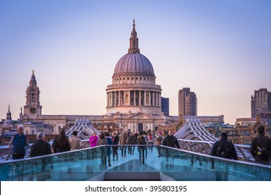 London, England - St.Paul's Cathedral and Millennium Bridge with Londoners walking through at sunset
