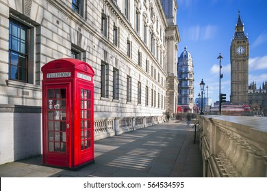 London, England - Traditional red british telephone box with Big Ben and Double Decker bus at the background on a sunny afternoon with blue sky and clouds