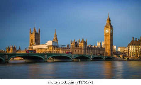 London, England - Traditional red double decker buses on Westminster Bridge with Big Ben and Houses of Parliament at sunrise