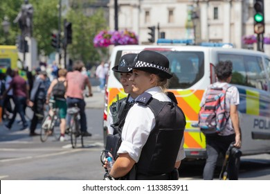 London, England, UK; 13th July 2018; Two Female Metropolitan Police Officers in the Street.  Unfocused Police Van Behind