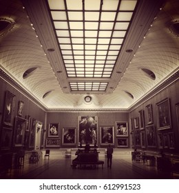London, England, UK - 14 July 2015: Interior of the Wallace Collection in Hertford House at Manchester Square, Marylebone, London. Long gallery lined with paintings and cove ceiling.  Sepia toned.