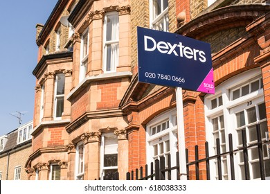 London, England, UK - April 2017: Estate agent sign outside a row of Victorian terraced houses in London. Dexters is London's leading independent Estate Agency with over 60 offices across London.