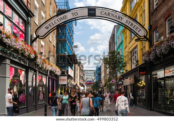 London, England, UK - August 4, 2014: People walking for shopping in Carnaby Street. Carnaby Street is a pedestrianised shopping street in Soho in the City of Westminster, Central London.