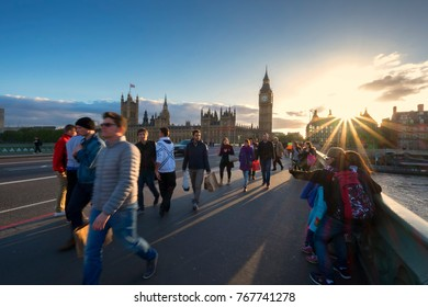 London, ENGLAND, UK - circa May 2014: Sunset at the Wesminster Bridge with the Big Ben and Parliament House on the background and moving traffic and people on the foreground. Contains motion blur.