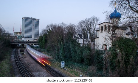 London, England, UK - February 2, 2014: A London Underground District Line train passes through Gunnersbury in West London, beside the Russian Orthodox Cathedral of the Dormition of the Mother of God.