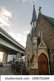 London, England, UK - February 2, 2014: St John The Evangelist church stands in the shadow the M4 Great West Road motorway flyover in Brentford in a contrasting juxtaposition of old and new.