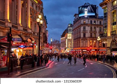 LONDON, ENGLAND, UK - FEBRUARY 2017: Rush hour and traffic near Piccadilly Circus with pedestrians walking in London's West End. Typical urban scenery in the center of London city under a cloudy sky.