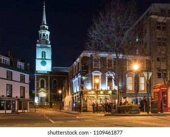 London, England, UK - February 9, 2018: The spire of St James's Church is lit up at night on Clerkenwell Green in central London.