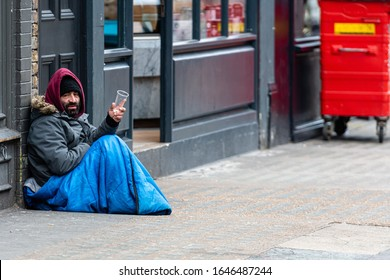 London, England, UK - January 2, 2020: a bearded man sitting on the sidewalk and begging from passersby