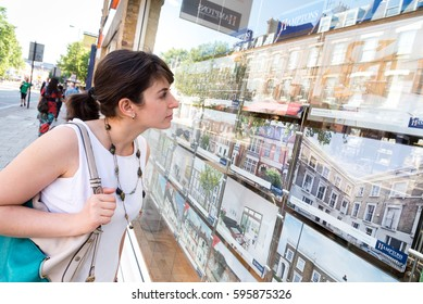 LONDON, ENGLAND, UK - JULY 19, 2013: Young woman looking at houses for sale in estate agent window in Islington, London