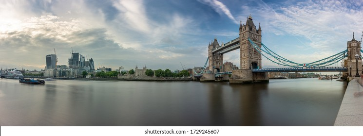 London, England, UK - June 1, 2018: The River Thames flows past the skyscrapers of the City of London and the Tower of London at Tower Bridge.