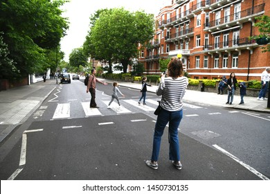 LONDON, ENGLAND, UK - JUNE 12: People crossing and taking pictures of the Abbey Road zebra crossing made famous by the 1969 Beatles album cover. London, UK, June 12, 2019