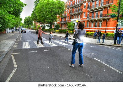 LONDON, ENGLAND, UK - JUNE 12: HDR image of people crossing and taking pictures of the Abbey Road zebra crossing made famous by the 1969 Beatles album cover. London, UK, June 12, 2019