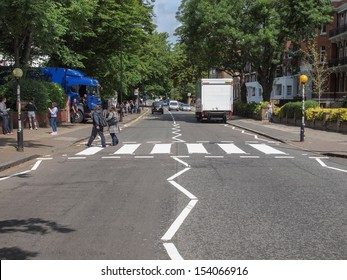 LONDON, ENGLAND, UK - JUNE 18: People crossing the Abbey Road zebra crossing made famous by the 1969 Beatles album cover on June 18, 2011 in London, England, UK