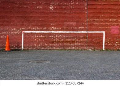 London, England, UK - March 20 2018 : Painted Goalpost Graffiti on Redbrick Wall with Orange Traffic Cone