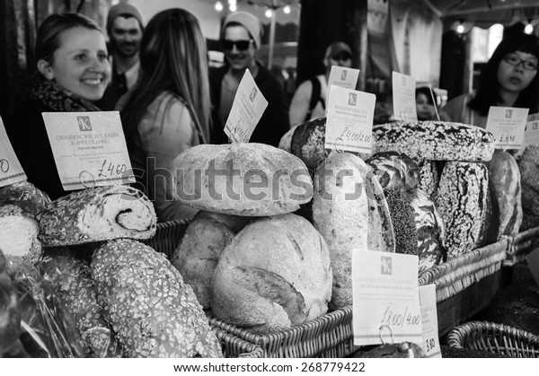 LONDON, ENGLAND, UK - MAY 3, 2014: Unidentified young people purchase bread at Karaway bakery in famous Borough Market. In last decades Borough Food Market became a fancy tourist attraction.