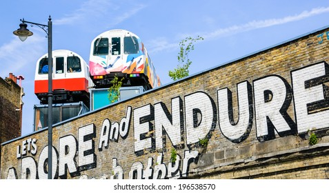 LONDON, ENGLAND, UK - MAY 4, 2014: Graffiti on the Village Underground wall and old colorful train wagons behind it in Brick Lane area. Urban art in this area attracts tourists from all over the world