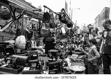 LONDON, ENGLAND, UK - MAY 4, 2014: Unidentified people with unidentified children shopping at the traditional flea market at Brick Lane. Brick Lane flea market operates every Sunday.