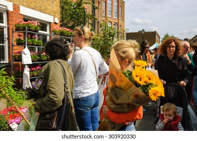LONDON, ENGLAND, UK - MAY 4, 2014: People buying flowers at Columbia Road Flower Market. This London's principal flower market is opened every Sunday.