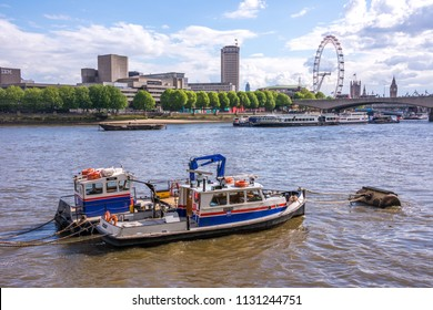 London, England, UK - may 8, 2014: Workboats at anchor on the River Thames and view of the city with the London Eye in the background