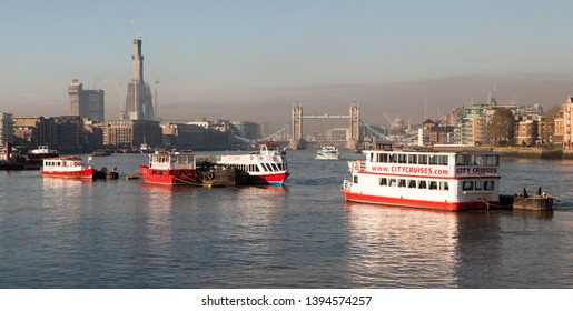 London, England, UK - November 16, 2010: The River Thames flows between Bermondsey and Wapping in East London with the City of London skyline behind, including construction of the Shard skyscraper.