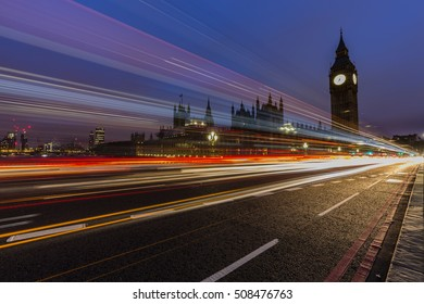 London, England, UK. Red buses blured in motion on Westminster bridge with Big Ben, the Palace of Westminster in early morning before sunrise.