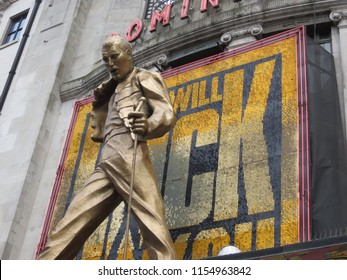 """London, England, United Kingdom – April 2013: The statue of Freddie Mercury above the West End's Dominion Theatre in London. Dominion Theatre is home to hit musical """"We Will Rock You""""."""