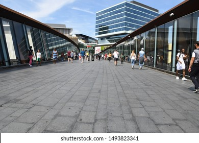LONDON , England / United Kingdom August 2019 People cross footbridge to Westfield Stratford City shopping centre.