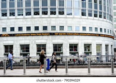 LONDON, ENGLAND-12 JULY 2013: People walk in front of the business buildings, Thomson Reuters, in Canary Wharf which is a major business district within the London Borough of Tower Hamlets, UK
