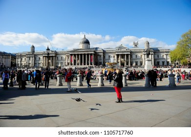 LONDON, ENGLAND-13 APRIL 2014: Crowded tourists in Trafalgar Square, the largest square in the City of Westminster London. It is so iconic and  this world famous site from sculptures to galleries, UK