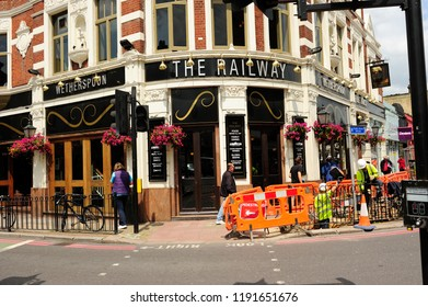 LONDON, ENGLAND-25 JUNE 2013: Undefined workers working on the pavement in front of  the beautiful building of Wetherspoons the Railway pub and restayrant Putney, South west London, United Kingdom
